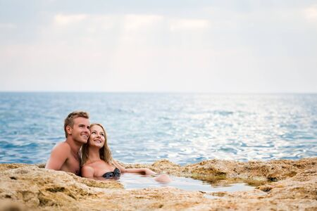 Young happy beautiful couple woman and man sitting in natural rock pool with water and smiling with sea at background on clear summer day. Travelling, vacations, romantic weekend, honeymoon concept 免版税图像
