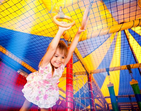 Small smiling girl in dress hanging on rings and feeling excited in playroom Stock fotó