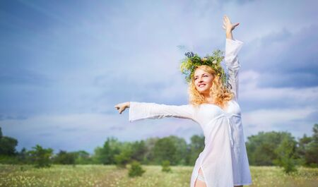 Young beautiful blond woman in white dress and wreath standing with eyes closed and enjoying sunshine on summer day with field landscape at background. Woman natural beauty and summer nature concept