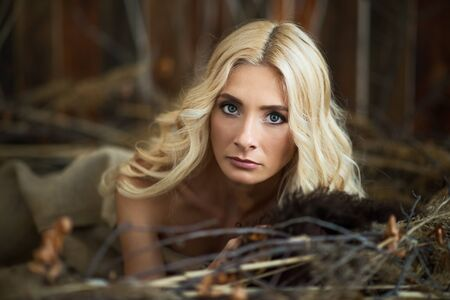 Portrait of woman with blonde hair and big green eyes lying near tree branches and looking at camera Фото со стока