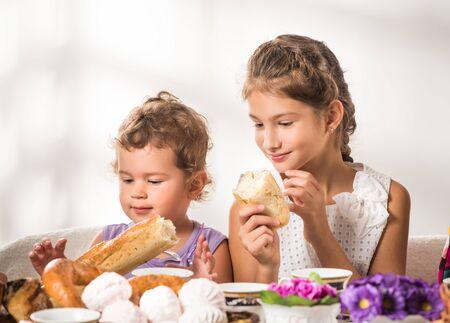 Lustige kleine Kinder essen frisches Brot und Brötchen
