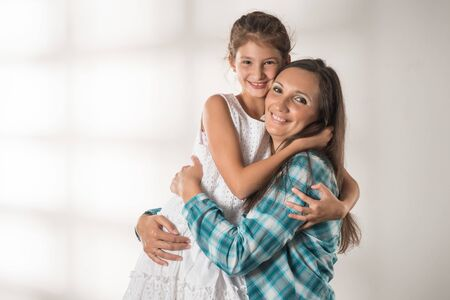 Young mother hugs her pretty positive daughter Archivio Fotografico
