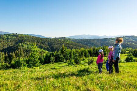 Joven madre y dos pequeñas hijas viajeros están parados en una pendiente con una hermosa vista de las colinas cubiertas de un denso bosque de abetos contra el cielo azul en un día soleado de verano. Concepto de turismo familiar