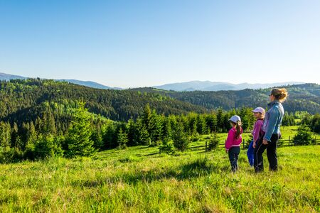 Young mother and two little daughters travelers stand on a slope with a gorgeous view of the hills covered with dense fir forest against the blue sky on sunny warm summer day. Family tourism concept