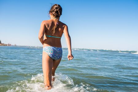Rear view of positive little girl running on the water among the noisy sea waves and looking into the distance beyond the horizon on sunny warm summer day. Concept of vacation and new experiences