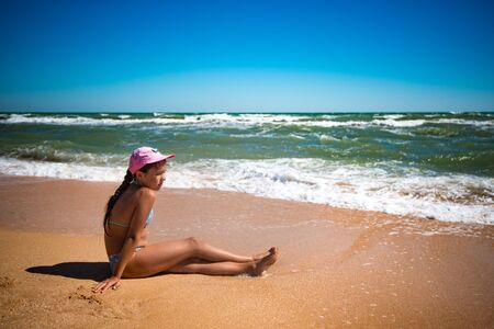 Happy beautiful little girl resting on the beach and playing with the sand on a sunny warm summer day. The concept of active games and healthy sea air