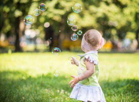 Klein babymeisje dat op gras loopt en bellen probeert te vangen
