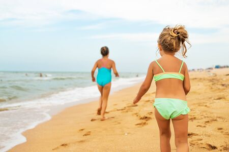 Two positive little girls run along sandy beach Foto de archivo