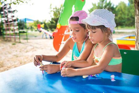 在户外玩玩偶的两个小逗人喜爱的女孩