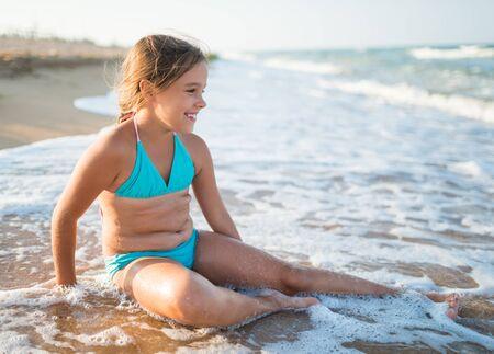 Pleased pretty little girl enjoys warm sea water