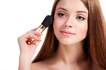 Girl applying blush with brush and looking away