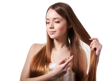 Girl with brown hair spraying perfume on her wrist