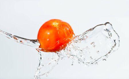 Foto en primer plano de tomate rojo en agua sobre fondo blanco, salpicaduras de agua y gotas alrededor Foto de archivo