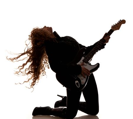 Woman squatting and clutching guitar Imagens