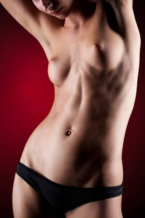 Topless girl in black underwear posing holding her hands behind her head and looking down. Photo with red background Stock Photo