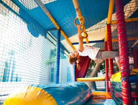 Girl hanging at colorful playground