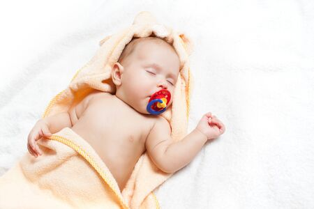 Adorable baby with pacifier taking nap.