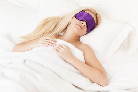 Top view of charming young lady in sleep mask taking nap in comfy bed. Attractive blonde girl lying under white warm blanket and seeing nice dreams. Concept of sleeping and bedtime. Foto de archivo