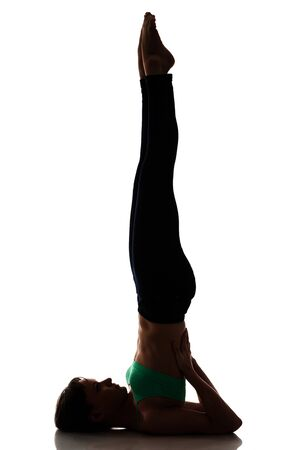 Side view of lady performing yoga exercise called salamba sarvangasana. Athletic girl lifting legs and supporting back by hands. Isolated on white studio background. Concept of supported shoulderstand. Foto de archivo