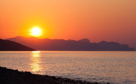 Scenic landscape of calm sea sun against the backdrop of high hills or mountains during summer vacation. The concept of travel to miserable countries. Place for advertising