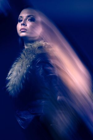 Portrait with blurry effect of young proud beautiful girl in leather jackets with a fur collar against a dark background. Concept of mysticism and mystery. Concept of advertising demi-season things