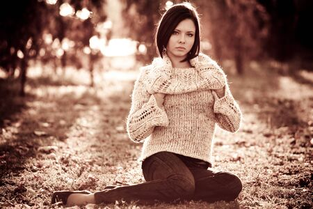 Monochrome photo of a pretty serious young woman in casual clothes sitting on a lawn in a park on sunny autumn warm day. Femininity and attractiveness concept Stock fotó
