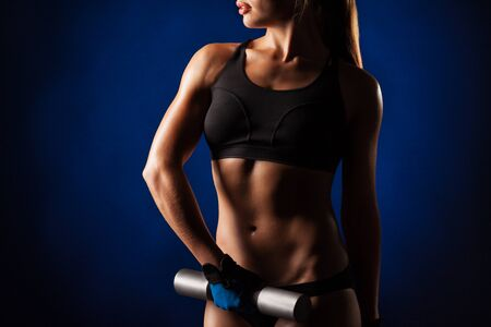 Unidentified Slender young girl fitness instructor in sportswear holds in her hands iron dumbbells in the studio on a dark blue background. Concept of a healthy muscular body. Advertising space