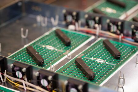 Metal components and microcircuits lie on metal compartments during the production of cases of future powerful supercomputers with video fruits. Concept production of specialized mining computers