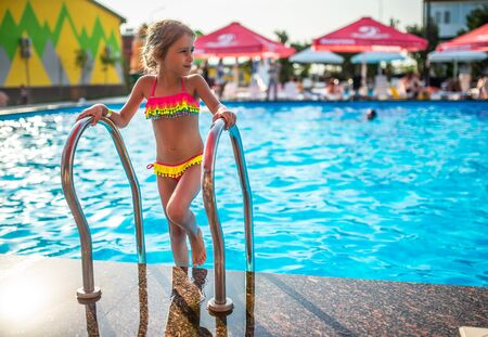 Happy little pretty girl in colored bathing suit