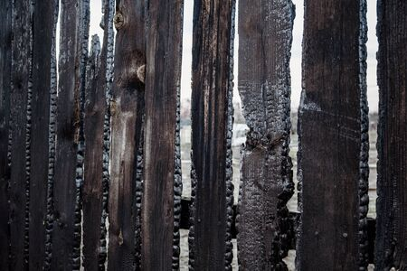 Burnt fence boards after a fire in a private house.