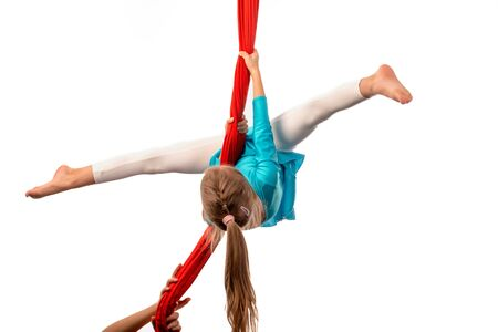 Little acrobat girl doing splits in the air