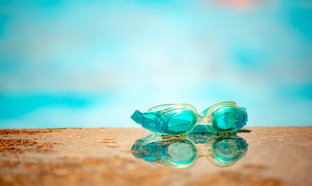 Close-up of waterproof children's swimming goggles lie on a wooden surface against the background of a blurred pool on a warm summer day. Concept of vacation with children at sea. Advertising space