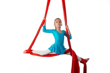 Little acrobat girl doing splits in the air