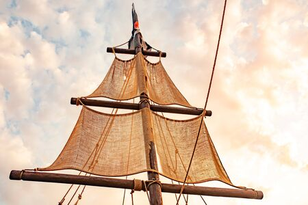 Bottom view of a ship mast with beige sails swings against a blue sky with sunny sunny summer warm day clouds. Marine and adventure concept