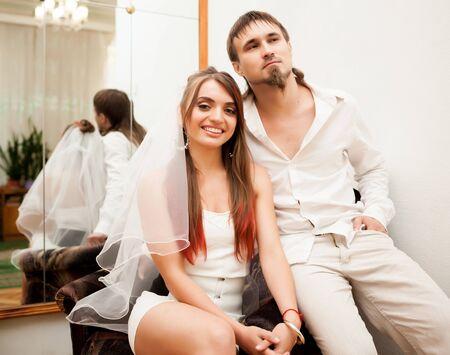 Beautiful newlyweds sitting in armchair.
