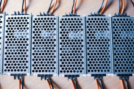 Top view of the metal mesh power supply of the microcircuit are on a wooden table at the production of high-tech computers. Concept of high technology and office equipment