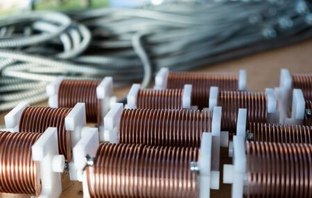 Close-up of high-frequency powerful copper wire on background of numerous blurry cables. Concept production of super modern high-tech components for transceiver appliances Stock Photo