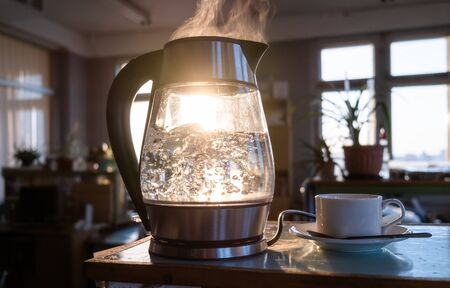 A transparent kettle of water boils against the background of the sunset shining through the window. The concept of coffee break and end of the working day.