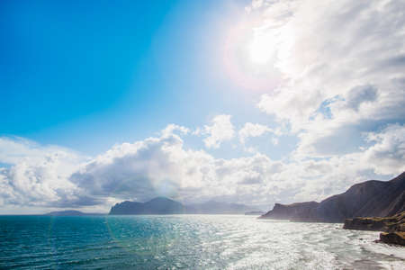 Sandy beach with mountains on background. Mountains are covered with grass, and has sheer cliffs from sea. Sky is cloudy