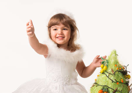 Front view of cute kids putting garland and fruits on artificial pine tree. Little girls wearing beautiful carnival dresses and headbands. Isolated on white studio background. Concept of christmas.