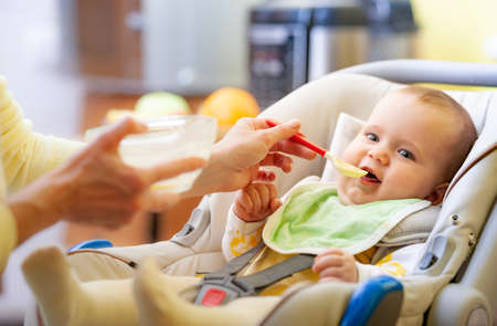 Cute young caring caucasian mother feeds her charming little six-month-old daughter in a cozy living room. The concept of endless worries during the decree