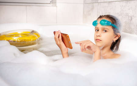 Funny little caucasian girl in swimming goggles surfs the Internet using a smartphone while swimming in the bathroom with foam at home. Children and home entertainment concept