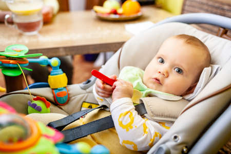 Side view of a smart little girl toddler sitting in a child seat and nibbling a toy while looking at mom. The concept of proper emotional development and childrens health