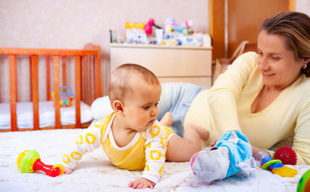 Cute cheerful kind mother plays with her charming six-month-old little daughter. The concept of early development of children and affection for mother 版權商用圖片