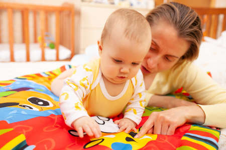 Close up of caring beautiful young mother teaches colors her six-month-old charming daughter lying in a cozy childrens room. The concept of care and parental love Banco de Imagens