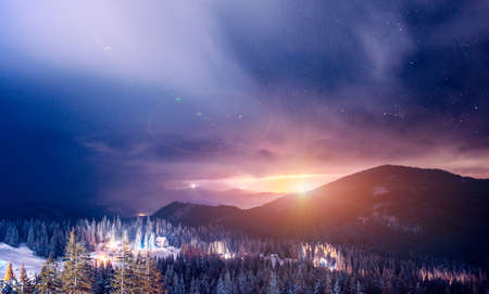 The resort ski resort illuminated at night is located in a picturesque place above a clear starry sky. Country Vacation Concept. Place for text