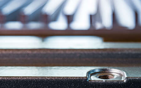 Close-up of a fluted metal surface with bolt hole on an unidentified automatic control device in a factory. The concept of secret military production Фото со стока