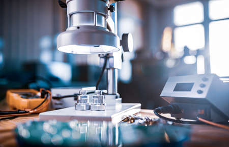 Large modern electron microscope. Microwave coaxial connector and electronic digital multimeter on workshop table. Research of high-frequency radio electronic components in a scientific laboratory