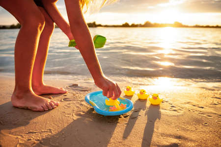 Unrecognizable kid playing with rubber duck toys on beach.