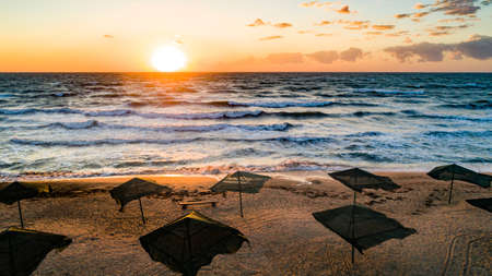 Beach umbrellas at sunrise. Sea current swims against the waves on the beautiful sea 写真素材